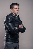 Young man, sideways, looking sideways ,leather jacket,. One young adult man only, standing sideways, looking sideways, leather jacket, studio, gray background royalty free stock photo