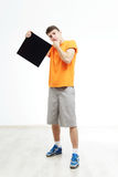 Young man with sign he is holding against a white background. Young rapper is holding a sign. Dancer is wearing in orange T-shirts with sign in a hand. Hip-hop stock photo