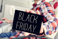 Young man with a signboard with the text black friday Royalty Free Stock Images