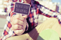 Young man with a signboard with the text never stop dreaming Royalty Free Stock Photography