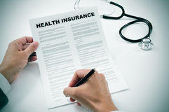 Young man signing a health insurance policy. Closeup of a young man signing a health insurance policy Stock Image