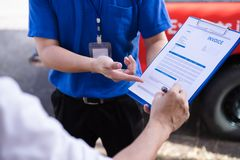 Young man signing invoice bill from delivery man after receiving parcel from courier at home. royalty free stock photos