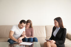 Young man signing papers sitting next to wife and realtor royalty free stock image