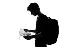 Young man silhouette backpacker reading map Stock Image
