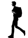 Young man silhouette backpacker walking. Young man backpacker walking silhouette in studio isolated on white background Royalty Free Stock Image
