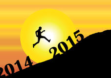 A young man silhouette jumping past 2014 into the new year 2015. On mountain with bright yellow sun & orange sky - evening sunset or morning sunrise concept Stock Image