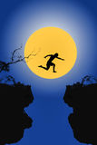 Young man in silhouette jumps between two cliffs on big moon  ba Royalty Free Stock Image