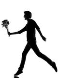 Young man silhouette offering flowers bouquet Stock Photos
