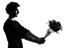 Young man silhouette offering flowers bouquet. Young man offering flowers bouquet silhouette in studio isolated on white background Royalty Free Stock Image