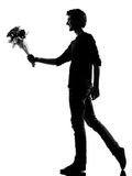 Young man silhouette offering flowers bouquet. Young man offering flowers bouquet silhouette in studio isolated on white background Stock Photography