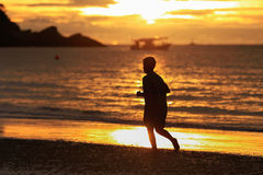 Young man silhouette running on beach in sunrise Stock Images