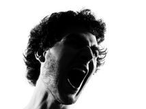 Young man silhouette screaming angry portrait. Young man screaming angry portrait silhouette in studio isolated on white background Stock Photos