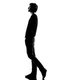 Young man silhouette walking Stock Photos