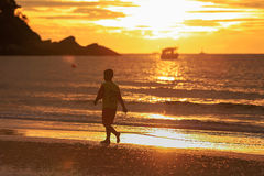 Young man silhouette walking on beach in sunrise. The young man silhouette walking on beach in sunrise stock photo