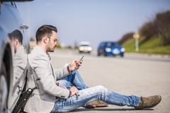 Young man with a silver car that broke down on the road Stock Photos