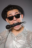 Young man in silver shirt and microphone isolated Royalty Free Stock Image