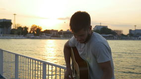 Young man singing at the guitar on the bridge over the sea stock video