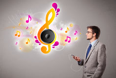 Young man singing and listening to music with musical notes Stock Images