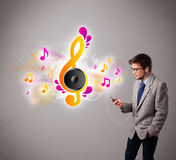 Young man singing and listening to music with musical notes Stock Photos