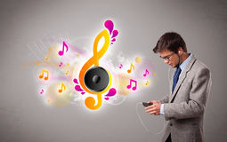 Young man singing and listening to music with musical notes Royalty Free Stock Image