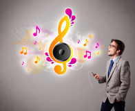Young man singing and listening to music with musical notes Royalty Free Stock Photos