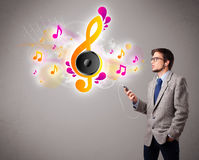 Young man singing and listening to music with musical notes Stock Image