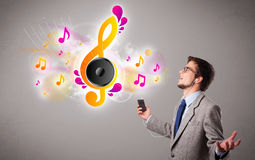 Young man singing and listening to music with musical notes Stock Photography