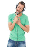 Young man singing into microphone with eyes closed Stock Photography