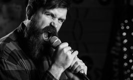 Young man singing with microphone. Hipster with beard stock images