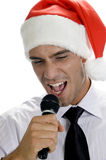 Young man singing into microphone with santa hat Royalty Free Stock Images