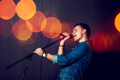Young Man Singing with Microphone. Stock Photos