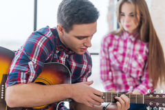 Young man singing playing guitar for his girlfriend Royalty Free Stock Image