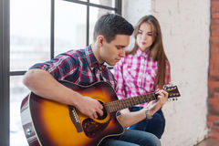 Young man singing playing guitar for his girlfriend Stock Photos