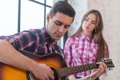 Young man singing playing guitar for his girlfriend Stock Image