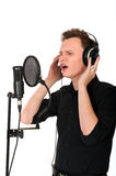 Young man singing song. Young man singing son to microphone in studio on white background stock photography