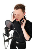 Young man singing song. To microphone in studio on white background stock image