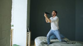 Young man singing to hair dryer and dancing rocknroll on bed in bedroom. Young man singing to hair dryer and dancing on bed in bedroom at home Royalty Free Stock Photo