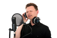 Young man singing to microphone. In studio on white background stock photo