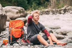 Young man sit barefoot on the mountain river bank Stock Image