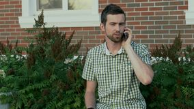 Young man sit on the bench and call to his friend using mobile phone. 4K stock footage