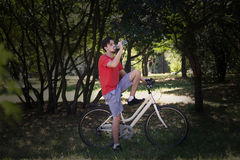Young man sit on bike in wood resting drink water Royalty Free Stock Photos