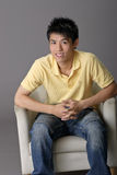 Young man sit on chair. Closeup portrait over gray background Stock Photo
