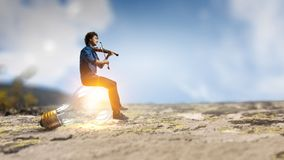 Find your inspiration. Mixed media. Young man sit on glass light bulb and playing violin. Mixed media royalty free stock image