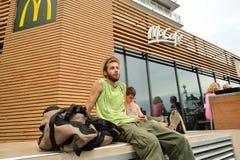 Young man sit near McDonald's restaurant Royalty Free Stock Photography