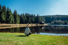 Young man sit on nice clean pond with wooden building and spring tree with blue sky royalty free stock photography