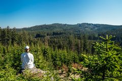 Young man sit on rock with forest and blue sky, looking to valley.  royalty free stock image