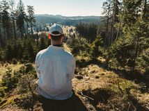 Young man sit on rock with forest, looking to valley.  royalty free stock photo