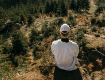 Young man sit on rock with forest, looking to valley, colored photo.  royalty free stock photography
