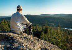 Young man sit on rock with forest and pond, looking to valley.  royalty free stock photos