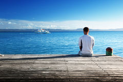 Young man siting on pier Royalty Free Stock Image